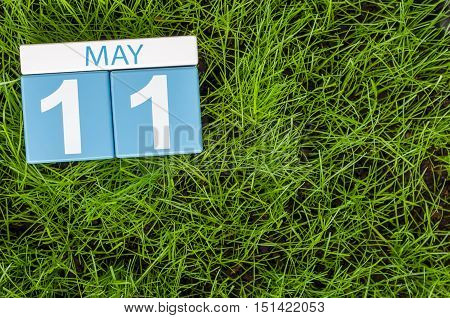 May 11th. Day 11 of month, calendar on football green grass background. Spring time, empty space for text.