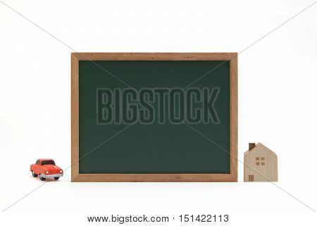 Miniature house, car, and blackboard on white background.