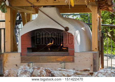 Old traditional stone bread oven stove with burning wood fire and red flames inside