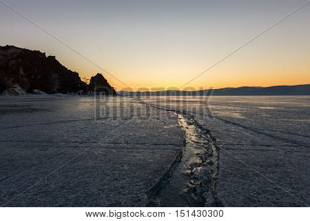 Wide Crack In The Ice Of Lake Baikal To The Shaman Rock