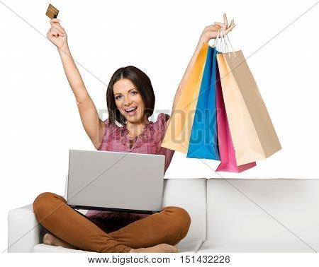 Ecstatic Woman Sitting on the Couch with Laptop, Credit Card and Shopping Bags