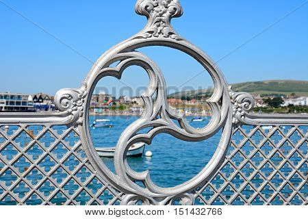Victorian decorative iron railings along the pier with the town to the rear Swanage Dorset England UK Western Europe.