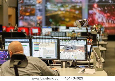 MOSCOW, RUSSIA - FEB 04, 2016: operator sitting at firm monitor nec in office room for passenger traffic monitoring, back view