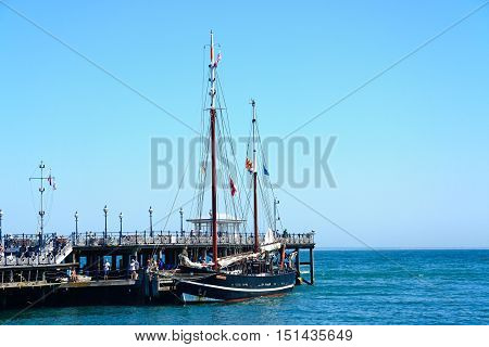 SWANAGE, UNITED KINGDOM - JULY 19, 2016 -The Moonfleet tallship moored alongside the Victorian pier Swanage Dorset England UK Western Europe, July 19, 2016.