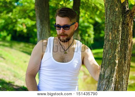 Portrait of a biker in a white t-shirt and sunglasses.