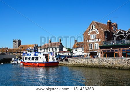 WAREHAM, UNITED KINGDOM - JULY 19, 2016 - Boats moored on the river with views towards The Old Granary and church Wareham Dorset England UK Western Europe, July 19, 2016.