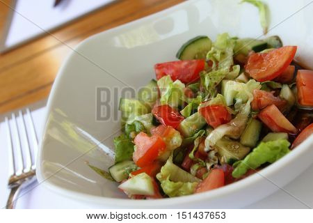 A plate of fresh salad of tomatoes, cucumbers and salad leaves
