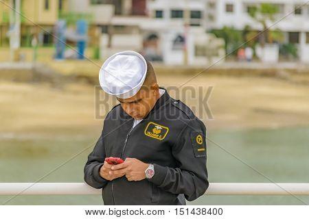 SALINAS, ECUADOR, OCTOBER - 2015 - Officer watching and concentrated on his chatting cellphone at Salinas Ecuador