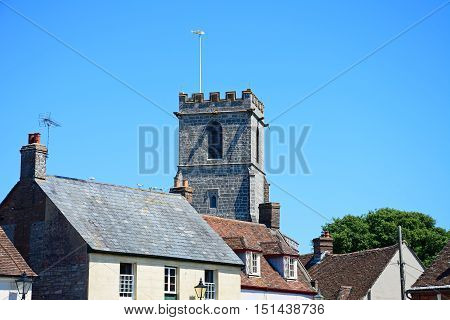 Lady St Mary parish church tower seen over shop buildings Wareham Dorset England UK Western Europe.