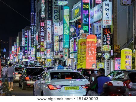 Busan South Korea - September 12th 2016: Busan the city centre evening illumination advertising fires a column of cars walk passers-by.
