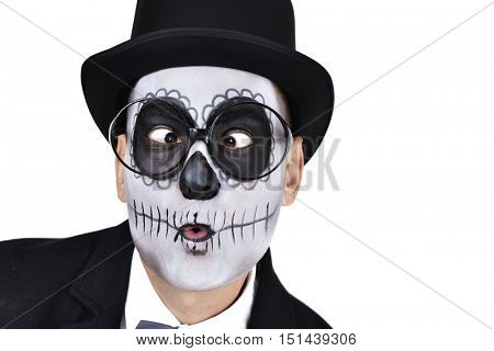 closeup of a man with a mexican calaveras makeup, wearing overcoat, bow tie, top hat and big round eyeglasses crossing his eyes, on a white background