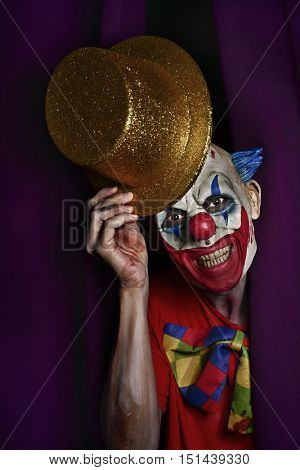 a scary evil clown peering out from a purple stage curtain, with a golden top hat in his hand