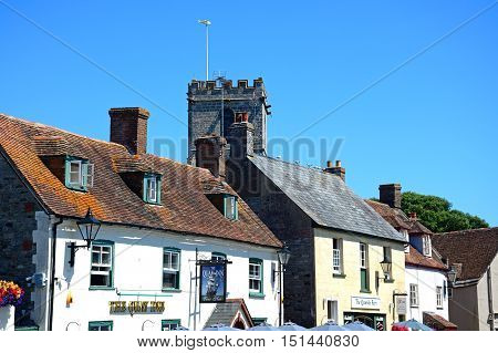 WAREHAM, UNITED KINGDOM - JULY 19, 2016 - The Quay Inn pub and shops with Lady St Mary church tower to the rear Wareham Dorset England UK Western Europe, July 19, 2016.