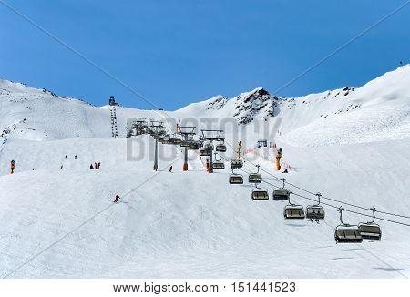 Skiers and chairlift in Alpine ski resort in Solden in Otztal Alps, Tirol, Austria