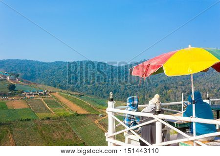 Three Tourists Sit On Viewpoint Of Phu Thap Boek --- Tourist Attraction In Petchabun Thailand poster