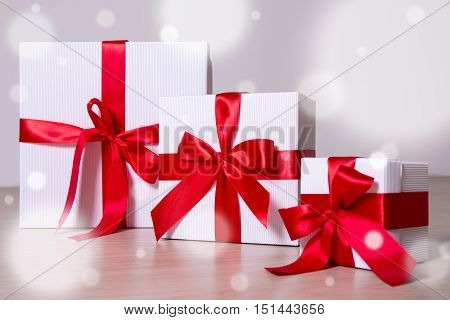 Winter Holiday Concept - White Gift Boxes With Red Ribbon On Wooden Background
