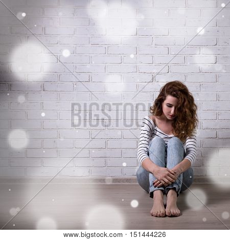 Winter Depression And Loneliness - Unhappy Woman Sitting On The Floor Over Brick Wall