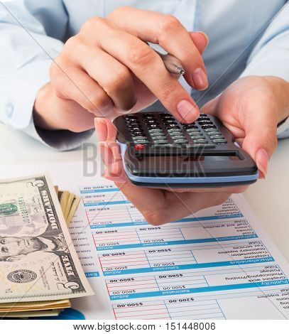 Close-up of a Businesswoman Analyzing Financial Figures with Calculator and Banknotes