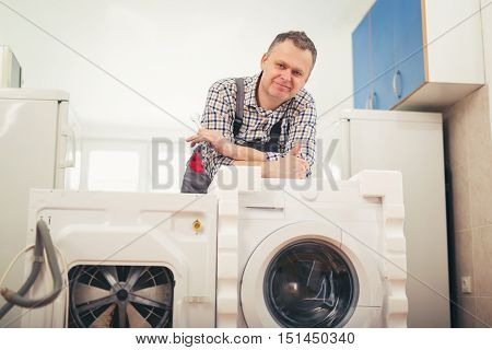 New washing machine and an old defective washing machine repairman in assembling washing machine