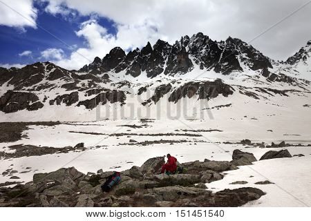 Hiker with dog resting on halt in snow mountain at gray day. Turkey Kachkar Mountains highest part of Pontic Mountains.