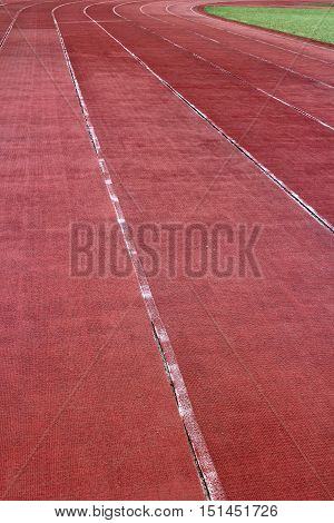 Running track lanes and grass field in vertical 3:2 format.