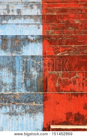 Blue and red concrete bleachers steps in vertical 3:2 format.