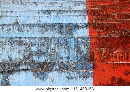 Blue and red concrete bleachers steps in horizontal 3:2 format.
