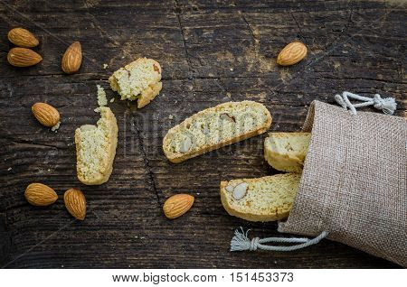 Italian cantuccini cookies with almond. Traditional italian almond cookies biscotti on old wooden background. Homemade Almond cookies on wooden table. Top view.