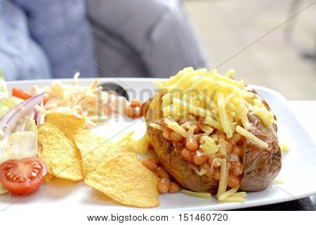 Jacket potato stuffed with baked beans and grated cheese served with a side salad and tortilla chips