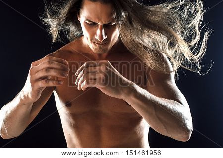 muscular man, clasps hands in fist, black background