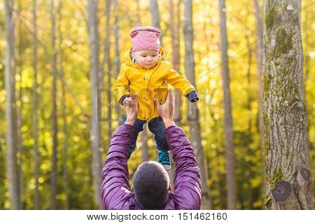 family, childhood, fatherhood, leisure and people concept - happy father and little son playing outdoors.