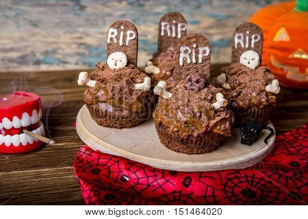 Halloween cupcakes with tombstone cake topper on an old wooden table. Small cupcakes with gravestone with the inscription RIP