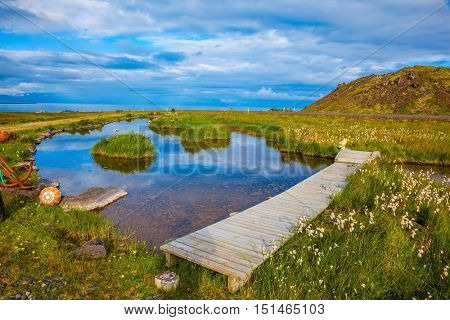 Lovely pond with thermal water. On small islands grows tall grass. Across the pond crossed by wooden walkways
