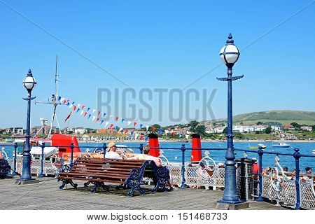 SWANAGE, UNITED KINGDOM - JULY 19, 2016 - Tourists sitting on a wooden bench along the Victorian pier with views towards the town Swanage Dorset England UK Western Europe, July 19, 2016.