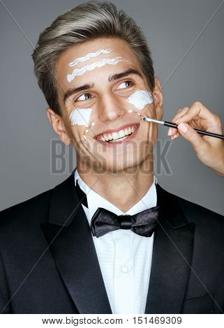 Happy imposing man with cream lines on face spa treatment. Portrait of elegant man with perfect skin. Grooming himself