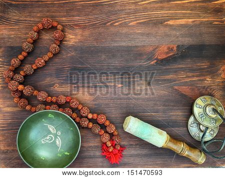Singing Bowl copper drums cymbals Rudraksha beads for meditation and relaxation on a wooden brown background top view