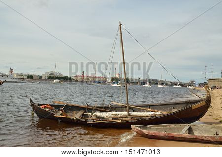 Wooden boat with drooping sailsmoored to the shore.
