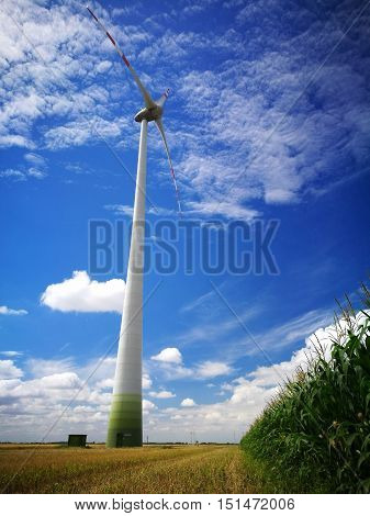 Windmill powerplant against landscape clouds and sky