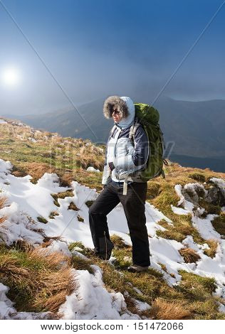 Woman Traveler with Backpack hiking in Mountains in clouds with beautiful morning landscape on background mountaineering sport lifestyle concept.