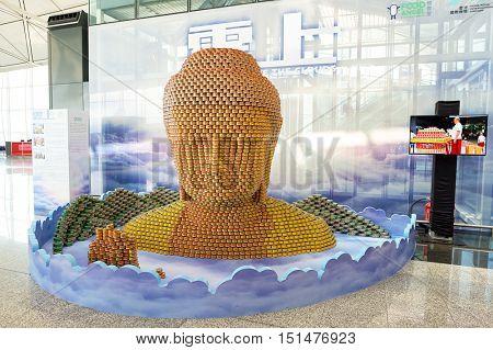 HONG KONG - NOVEMBER 03, 2015: Buddha sculpture made of Tuna salad cans at Hong Kong Airport. Hong Kong International Airport is the main airport in Hong Kong.