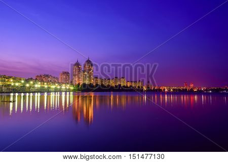 Embankment of modern european city with night illumination and colorful sky. Evening at the Dnieper river in Obolon, Kiev