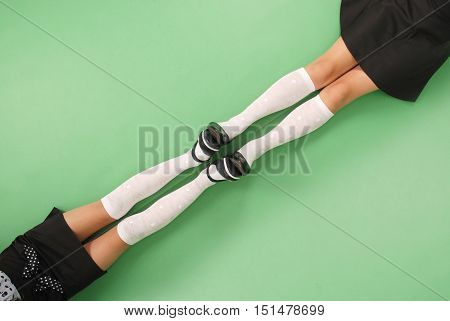 Two girls in knee-length socks isolated on green background