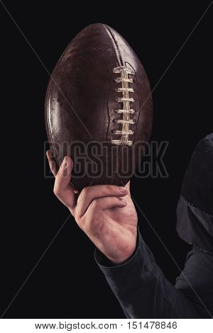 Soccer player on a dark background in vintage style. The classic American game. college Students. close-up ball
