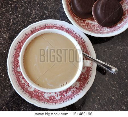 Coffee with milk in a fine bone china cup with chocolate cookies