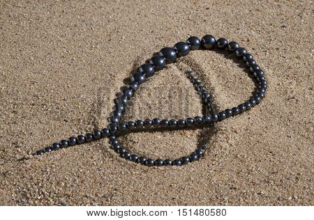 hematite beads lie on the sand in the sun