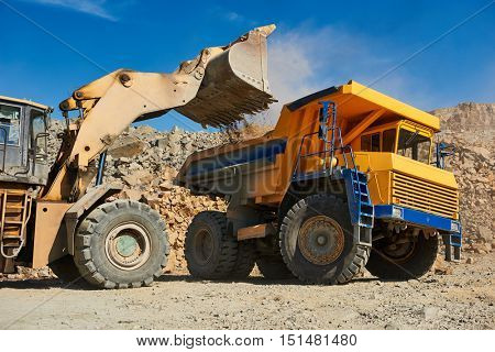 Wheel loader loading ore into dump truck at opencast poster