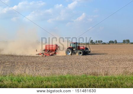 Tractor on the field. Plowing. Dust on the field. Excavation. Red Tractor. Plow