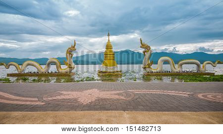Golden pagoda surrounded by 2 figures of naga with the sky, white cloud, sunlight and mountain in Phayao lake (Kwan Phayao) as background. This place is located in Phayao in the northern of Thailand.