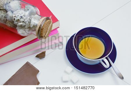 tea and chocolate on the table with book and potpourri. relax time.