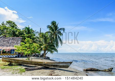 Livingston Guatemala - August 31 2016: Boat pulled ashore on beach in Caribbean town of Livingston